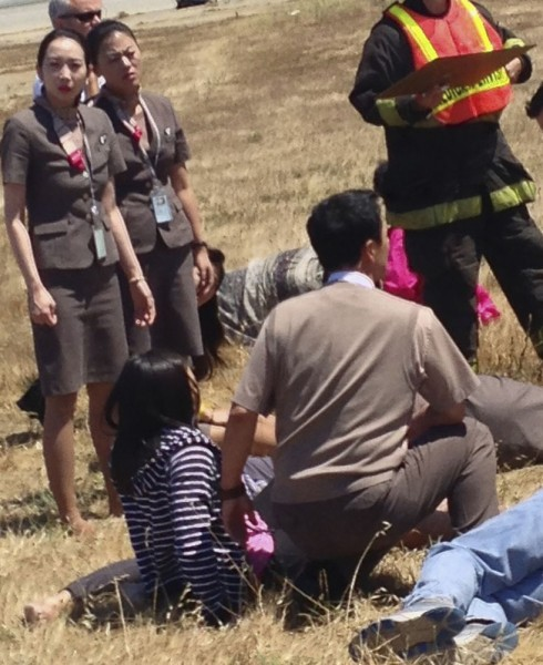 Asiana Airlines flight attendant Kim Ji-yeon stands near a runway with rescued passengers in San Francisco
