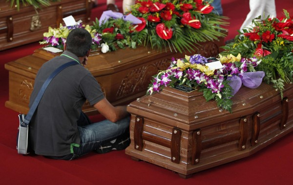 A man sits next to the coffins of victims of a coach crash during the funeral service at the Monteruscello Palasport