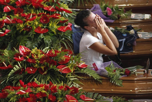 A woman cries next to coffins of victims of coach crash during funeral service at Monteruscello Palasport near Pozzuoli