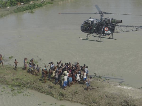 Flood-affected people gather under an Indian Army helicopter carrying relief materials at the flooded area of Sunipur district in Assam