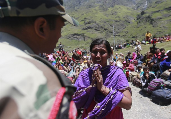 A survivor pleads with a soldier to allow her mother to board an army helicopter during rescue operations at Badrinath in the Himalayan state of Uttarakhand
