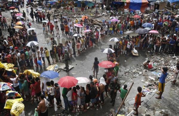 131114-supertyphoon-haiyan-philippines-tacloban-queue-food-001