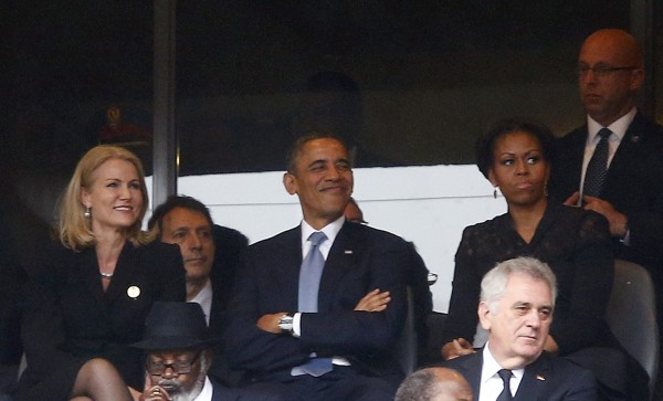 U.S. President Obama and Danish PM Thorning-Schmidt smile as his wife, U.S. first lady Michelle looks on during memorial service for late South African President Nelson Mandela in Johannesburg