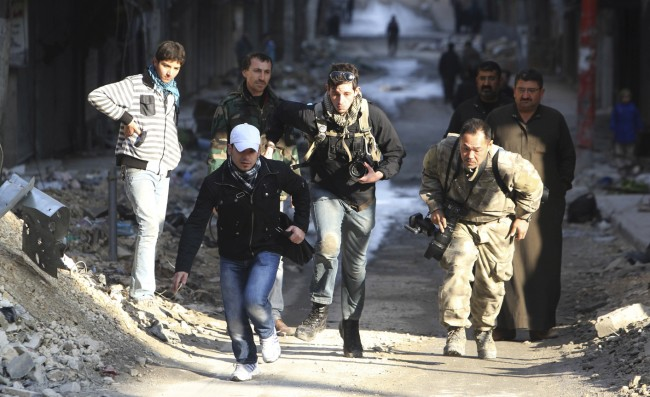 Journalists Karcha and Fujimoto run for cover next to an unidentified fixer in a street in Aleppo's district of Salaheddine