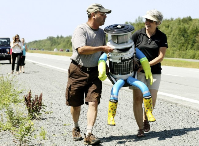 Anne Saulnier and her husband Brian carry the anthropomorphic robot named hitchBOT to their truck on Highway 102 outside of Halifax