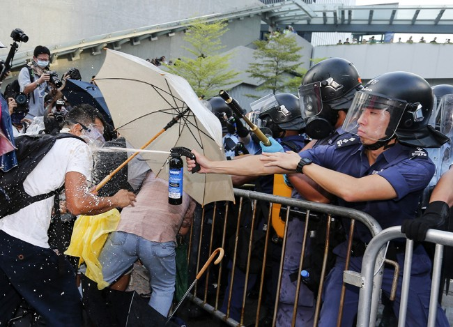 A riot policeman uses pepper spray during clash with protesters, as tens of thousands of protesters block the main street to the financial Central district outside the government headquarters in Hong Kong