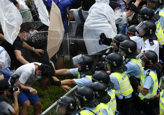 Riot police use pepper spray as they clash with protesters, as tens of thousands of protesters block the main street to the financial Central district outside the government headquarters in Hong Kong