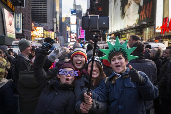 A family takes a selfie during New Year's Eve celebrations in Times Square, New York