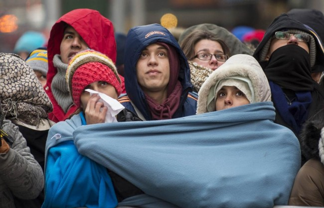 Revelers are huddled in a blanket in Times Square during New Year's Eve celebrations in New York