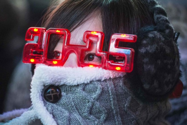 A woman wears 2015 glasses while taking cover from the cold weather during New Year's Eve celebrations in Times Square, New York