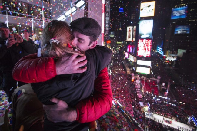 A couple embraces on a balcony amidst confetti after the clock strikes midnight during New Year's Eve celebrations in Times Square, New York