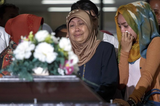 The mother and other family members of a passenger of Airasia QZ8501 cry upon receiving her remains at Bhayankara Hospital in Surabaya