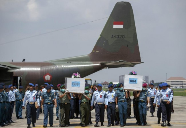 Indonesian military personnel carry caskets containing the remains of passengers onboard AirAsia flight QZ8501 at a military base in Surabaya