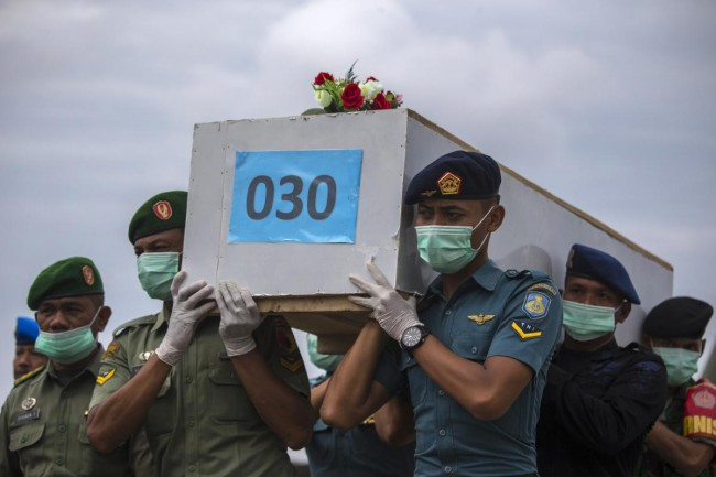 Indonesian military personnel carry a casket containing the remains of a passenger onboard AirAsia flight QZ8501, recovered off the coast of Borneo, at a military base in Surabaya