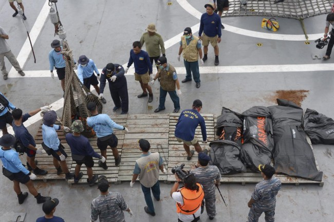 Indonesian Navy personnel lay recovered dead bodies from AirAsia flight QZ8501 on the the deck of the Indonesian Navy vessel KRI Banda Aceh, at sea