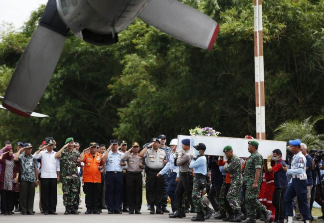 Caskets containing the remains of passengers from AirAsia QZ8501 are carried into an Indonesian military cargo plane to be transported  back to Surabaya, at the airport in Pangkalan Bun