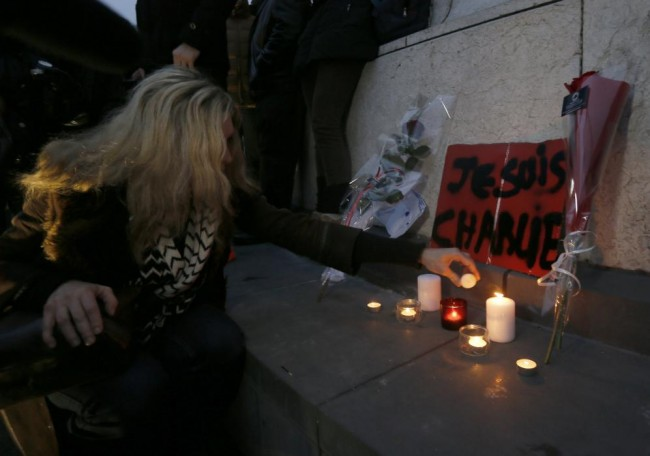 """A woman places candles next to flowers and a placard which reads """"I am Charlie"""" displayed to pay tribute during a gathering at the Place de la Republique in Paris"""
