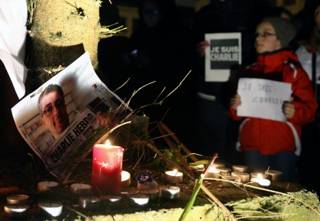 People pay tribute to the victims of a shooting by gunmen at the offices of weekly satirical magazine Charlie Hebdo in Paris, in front of the European Parliament in Brussels