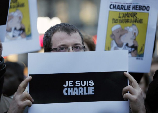 """A man holds a placard which reads """"I am Charlie"""" during a gathering at the Place de la Republique in Paris"""