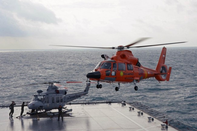 An Indonesian search and rescue helicopter prepares for landing during operations to lift the tail of AirAsia flight QZ8501 from the Java sea