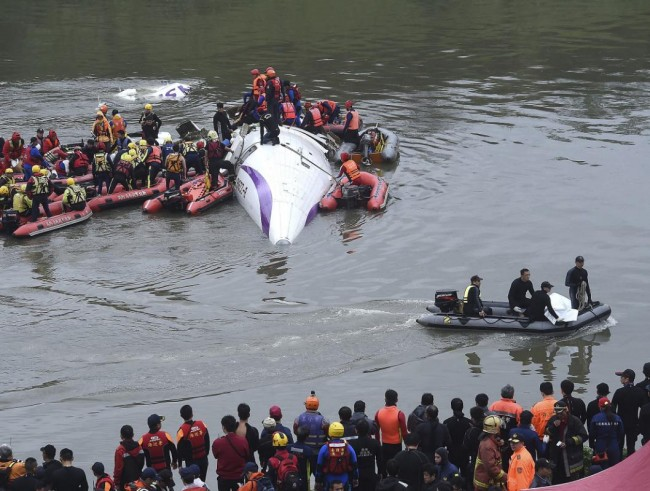 Rescuers remove a body by boat after a TransAsia Airways plane crash landed in a river in New Taipei City