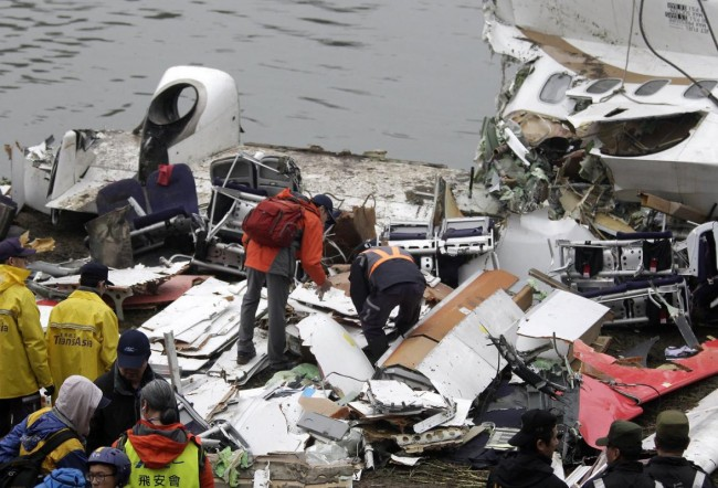 Rescue personnel examine the wreckage of TransAsia Airways plane Flight GE235 after it crash landed into a river, in New Taipei City