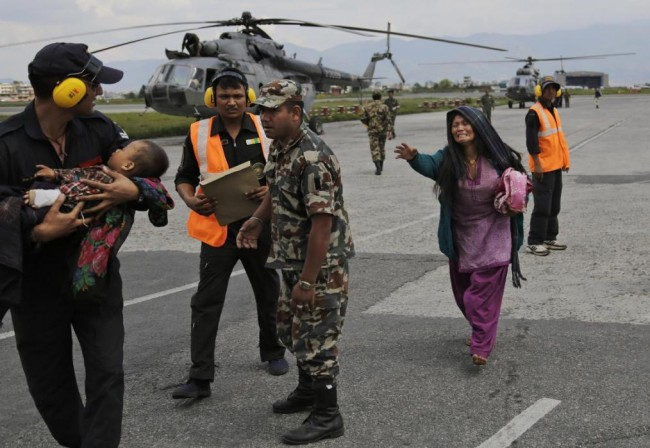 An Indian Air Force person walks carrying a Nepalese child, wounded in Saturday's earthquake, to a waiting ambulance as the mother rushes to join after they were evacuated from a remote area at the airport in Kathmandu, Nepal, Monday, April 27, 2015. The death toll from Nepal's earthquake is expected to rise depended largely on the condition of vulnerable mountain villages that rescue workers were still struggling to reach two days after the disaster.  (AP Photo/Altaf Qadri)