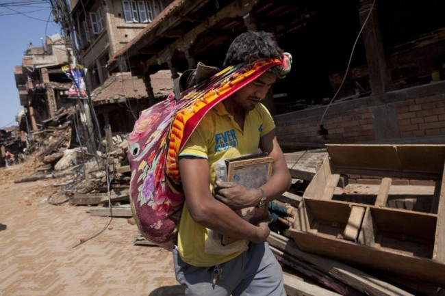 A Nepalese man carries his belongings from earthquake debris in Bhaktapur, on the outskirts of Kathmandu, Nepal, Monday, April 27, 2015. A strong magnitude earthquake shook Nepal's capital and the densely populated Kathmandu valley on Saturday devastating the region and leaving tens of thousands shell-shocked and sleeping in streets. (AP Photo/Niranjan Shrestha)
