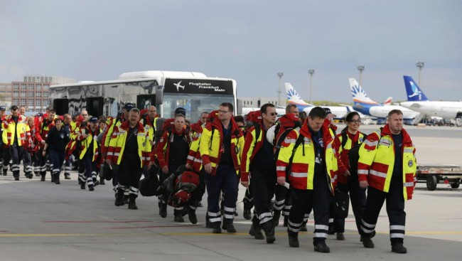 Members of Germany's NGO organistation International Search and Rescue (ISAR- Germany) arrive to board their flight to Nepal via Delhi, at Frankfurt airport April 26, 2015. Some seven rescue dogs, 51 doctors, medics and logistical experts are flying to Nepal on Sunday, a day after a 7.9 magnitude earthquake devastated the heavily crowded Kathmandu Valley, killing more than 2,200 people, and triggered a deadly avalanche on Mount Everest.  REUTERS/Wolfgang Rattay