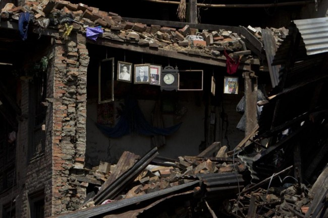 Portraits and a wall clock is seen hanging on the remains of a house damaged in Saturday's earthquake in Bhaktapur, on the outskirts of Kathmandu, Nepal, Monday, April 27, 2015. A strong magnitude earthquake shook Nepal's capital and the densely populated Kathmandu valley on Saturday devastating the region and leaving tens of thousands shell-shocked and sleeping in streets. (AP Photo/Niranjan Shrestha)