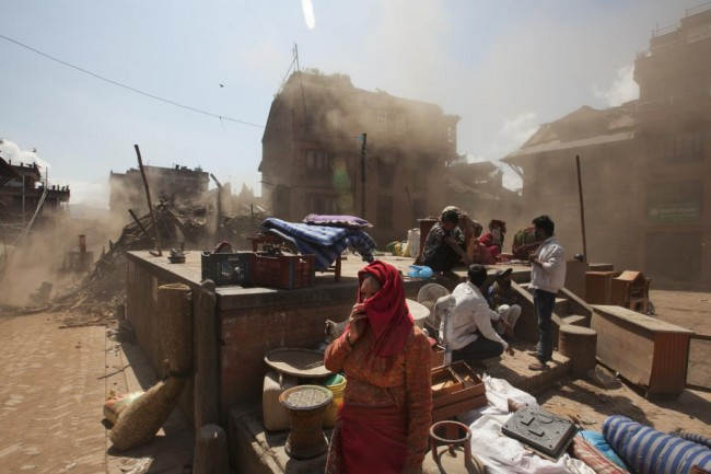 Nepalese residents gather in an open space at the site of destruction caused after Saturday's earthquake in Bhaktapur, on the outskirts of Kathmandu, Nepal, Monday, April 27, 2015. A strong magnitude earthquake shook Nepal's capital and the densely populated Kathmandu valley on Saturday devastating the region and leaving tens of thousands shell-shocked and sleeping in streets. (AP Photo/Niranjan Shrestha)