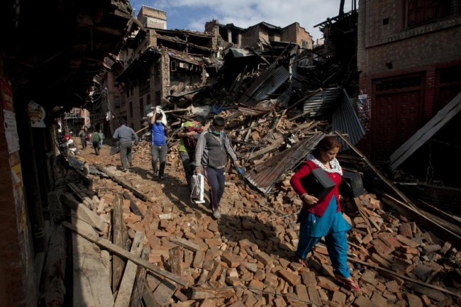 Nepalese residents carry belongings from their destroyed homes as they walk through debris of Saturday's earthquake, in Bhaktapur on the outskirts of Kathmandu, Nepal, Monday, April 27, 2015. A strong magnitude earthquake shook Nepal's capital and the densely populated Kathmandu valley on Saturday devastating the region and leaving tens of thousands shell-shocked and sleeping in streets. (AP Photo/Niranjan Shrestha)