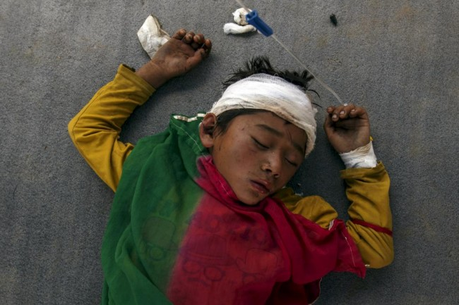 An injured boy sleeps on the ground outside the overcrowded Dhading hospital, in the aftermath of Saturday's earthquake, in Dhading Besi, Nepal April 27, 2015. REUTERS/Athit Perawongmetha       TPX IMAGES OF THE DAY