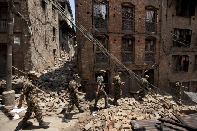 Members of the Nepalese army walk through a damaged area caused by Saturday's earthquake, in Bhaktapur, on the outskirts of Kathmandu, Nepal, Monday, April 27, 2015. A strong magnitude earthquake shook Nepal's capital and the densely populated Kathmandu valley on Saturday devastating the region and leaving tens of thousands shell-shocked and sleeping in streets. (AP Photo/Niranjan Shrestha)