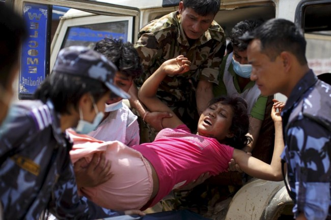 Military personnel and volunteers carry an injured woman into Dhading hospital, in the aftermath of Saturday's earthquake, in Dhading Besi, Nepal April 27, 2015.  REUTERS/Athit Perawongmetha