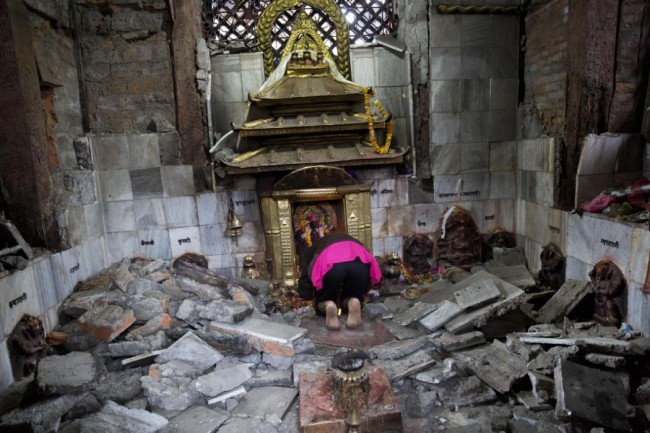 A Hindu Nepalese woman offers prayers at Indrayani temple, that was damaged in Saturday's earthquake, in Kathmandu, Nepal, Monday, April 27, 2015. A strong magnitude earthquake shook Nepal's capital and the densely populated Kathmandu valley on Saturday devastating the region and leaving tens of thousands shell-shocked and sleeping in streets. (AP Photo/Bernat Armangue)