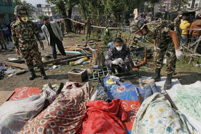 Rescue teams' members identify bodies dug out of the collapsed Sitapyla church in Kathmandu, Nepal, Monday, April 27, 2015. A strong magnitude 7.8 earthquake shook Nepal's capital and the densely populated Kathmandu Valley on Saturday, causing extensive damage with toppled walls and collapsed buildings. (AP Photo/Wally Santana)