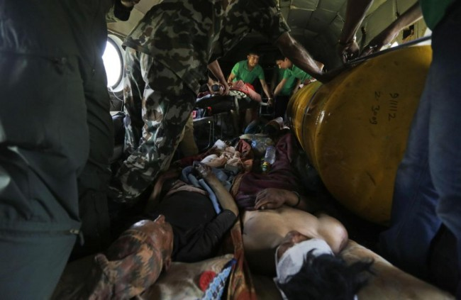 Nepalese victims of Saturday's earthquake lie inside an Indian air force helicopter as they are evacuated from Trishuli Bazar to Kathmandu airport in Nepal, Monday, April 27, 2015. The death toll from Nepal's earthquake is expected to rise depended largely on the condition of vulnerable mountain villages that rescue workers were still struggling to reach two days after the disaster.  (AP Photo/Altaf Qadri)