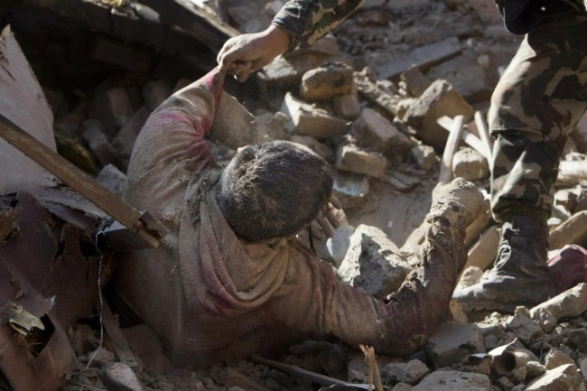 EDS NOTE GRAPHIC CONTENT - Members of Nepalese army rescue a dead body from inside a building that collapsed in Saturday's earthquake, in Bhaktapur, on the outskirts of Kathmandu, Nepal, Monday, April 27, 2015. A strong magnitude earthquake shook Nepal's capital and the densely populated Kathmandu valley on Saturday devastating the region and leaving tens of thousands shell-shocked and sleeping in streets. (AP Photo/Niranjan Shrestha)