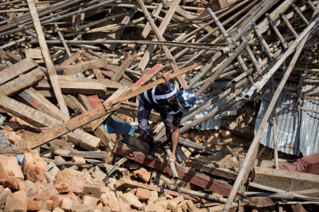 A member of Nepalese police personnel tries to clear the rubble with his hands while looking for survivors at the compound of a collapsed temple, in the aftermath of Saturday's earthquake in Kathmandu, Nepal, April 27, 2015. REUTERS/Danish Siddiqui