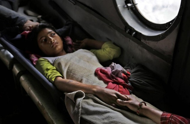 A Nepalese girl injured in Saturday's earthquake holds the hand of her mother inside an Indian air force helicopter as they are evacuated from Trishuli Bazar to Kathmandu airport in Nepal, Monday, April 27, 2015. The death toll from Nepal's earthquake is expected to rise depended largely on the condition of vulnerable mountain villages that rescue workers were still struggling to reach two days after the disaster.  (AP Photo/Altaf Qadri)
