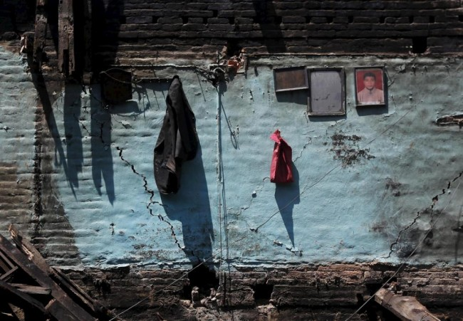 A coat and a framed portrait are seen hanging on a cracked wall of a damaged house after an earthquake in Bhaktapur, Nepal April 27, 2015. REUTERS/Adnan Abidi