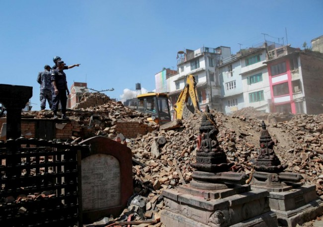 Nepalese police personnel look on as an excavator is used to dig through rubble to search for bodies following Saturday's earthquake in Kathmandu, Nepal, April 27, 2015. REUTERS/Danish Siddiqui