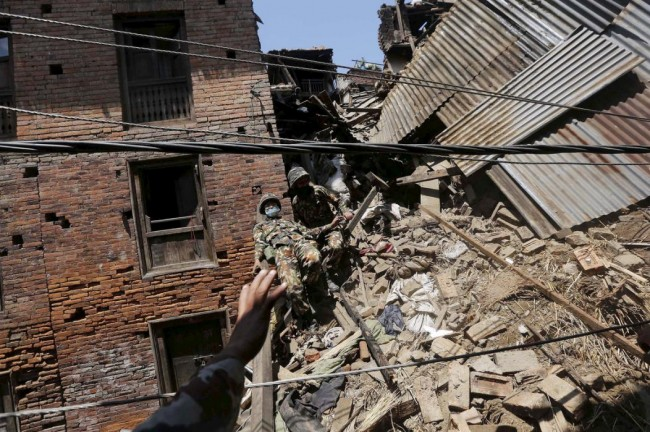 A Nepalese army soldier loses his balance while descending from a mound of rubble during the recovery of a body from a house, in the aftermath of Saturday's earthquake in Bhaktapur, Nepal April 27, 2015. REUTERS/Adnan Abidi