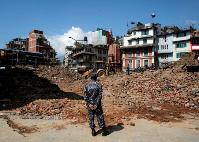 A member of Nepalese police personnel looks on as an excavator is used to dig through rubble to search for bodies, in the aftermath of Saturday's earthquake in Kathmandu, Nepal, April 27, 2015. REUTERS/Danish Siddiqui