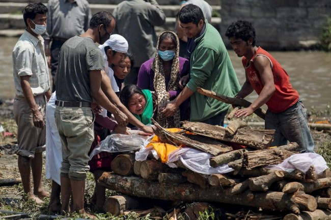 A woman cries as her father's body is prepared for cremation along a river, following Saturday's earthquake, in Kathmandu, Nepal, April 27, 2015. The man died during the 7.9 magnitude earthquake that hit the country on Saturday.    REUTERS/Danish Siddiqui      TPX IMAGES OF THE DAY