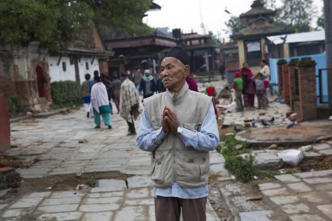 Un anciano nepalí reza junto a un edificio dañado (no fotografiado)en el terremoto que sacudió el país el sábado, en Katmandú, Nepal, el 27 de abril de 2015. (Foto AP/Bernat Armangue)