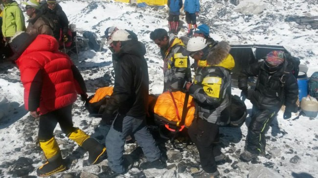 In this Sunday, April 26, 2015 photo, a person critically injured in an avalanche is carried on a stretcher to be evacuated out of Everest Base Camp, Nepal. An avalanche on Saturday, set off by the massive earthquake that struck Nepal, left more than a dozen people dead and dozens more injured. (AP Photo/Nima Namgyal Sherpa)