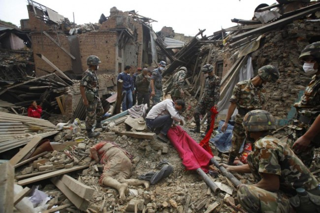 A dead body of a woman is seen after rescue workers recovered it from debris following Saturday's earthquake in Bhaktapur near Kathmandu, Nepal, Sunday, April 26, 2015. A strong earthquake shook Nepal's capital and the densely populated Kathmandu Valley before noon Saturday, causing extensive damage with toppled walls and collapsed buildings, officials said. (AP Photo/Niranjan Shrestha)