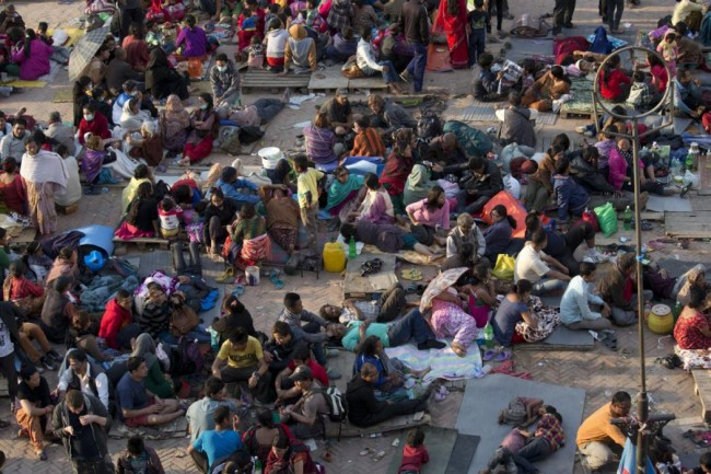 People gather on an open space for security reasons at Basantapur Durbar Square, damaged in Saturday's earthquake, in Kathmandu, Nepal, Sunday, April 26, 2015. The earthquake centered outside Kathmandu, the capital, was the worst to hit the South Asian nation in over 80 years. It destroyed swaths of the oldest neighborhoods of Kathmandu, and was strong enough to be felt all across parts of India, Bangladesh, China's region of Tibet and Pakistan. (AP Photo/Bernat Armangue)